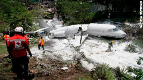 Broken in half, the jet lies engulfed in foam sprayed by Honduran firefighters.