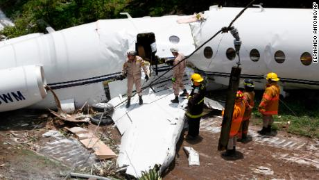 Emergency crew work at the wreckage site where a private jet crashed, in Tegucigalpa, Honduras, Tuesday, May 22, 2018. The white Gulfstream jet crashed off the end of the runway at Tegucigalpa's airport Tuesday, but the crew and passengers were rescued and reportedly out of danger, according to Honduras emergency management agency.(AP Photo/Fernando Antonio)