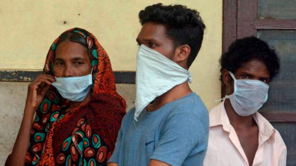 Indians standing in a queue outside the Government Medical College hospital in Kozhikode wear masks as a precaution against the Nipah virus.
