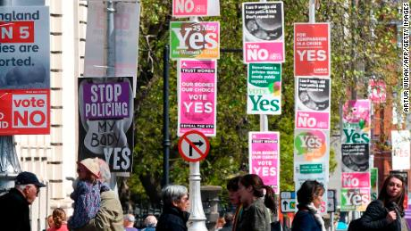 People cross the road past posters urging a yes vote in the referendum to repeal the eighth amendment of the Irish constitution, a subsection that effectively outlaws abortion in most cases, and posters calling for a no vote in the referendum near the government buildings in Dublin on May 12, 2018. - Ireland will hold a referendum on May 25 on whether to alter its constitution to legalise abortion. The Eighth Amendment of the Irish constitution recognises the equal right to life of the unborn and the mother. Abortion is illegal unless there is a real and substantial risk to the life of the mother, and a woman convicted of having an illegal termination faces 14 years imprisonment. (Photo by Artur Widak / AFP)        (Photo credit should read ARTUR WIDAK/AFP/Getty Images)