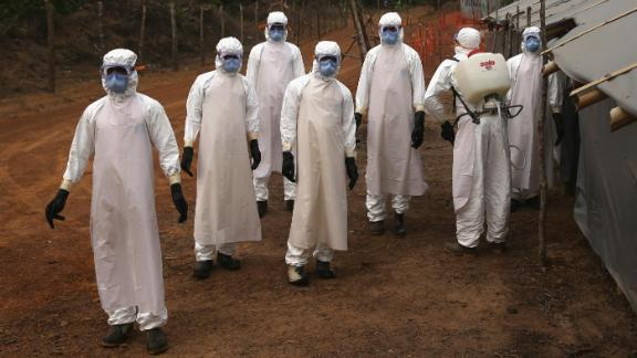 """DISCO HILL, LIBERIA - JANUARY 27:  A burial team awaits decontamination at the U.S.-built cemetery for """"safe burials"""" on January 27, 2015 in Disco Hill, Liberia."""