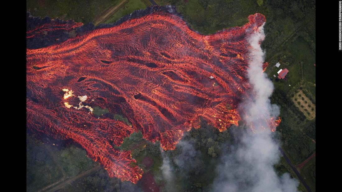 "Lava from the Kilauea volcano approaches a home in Pahoa, Hawaii, on Saturday, May 19. <a href=""https://www.cnn.com/interactive/2018/05/us/hawaii-kilauea-volcano-eruption-cnnphotos/"" target=""_blank"">The volcano erupted</a> earlier this month, sending lava into residential areas of the Big Island."