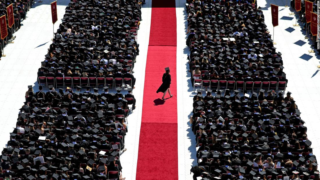 A graduate crosses a red carpet during Boston College's commencement ceremony on Monday, May 21.