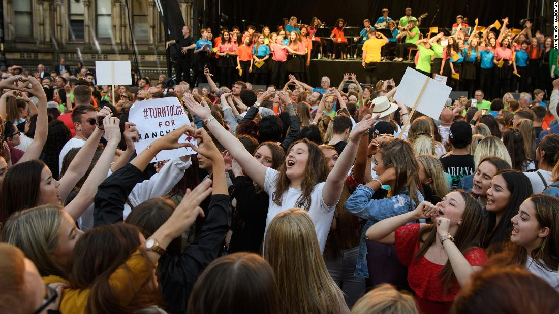 "A group of young women sing and dance during a concert in Manchester, England, on Tuesday, May 22. The concert was held <a href=""https://www.cnn.com/2018/05/22/europe/manchester-bombing-anniversary-intl/index.html"" target=""_blank"">one year after the terrorist attack</a> that claimed 22 lives at an Ariana Grande concert."