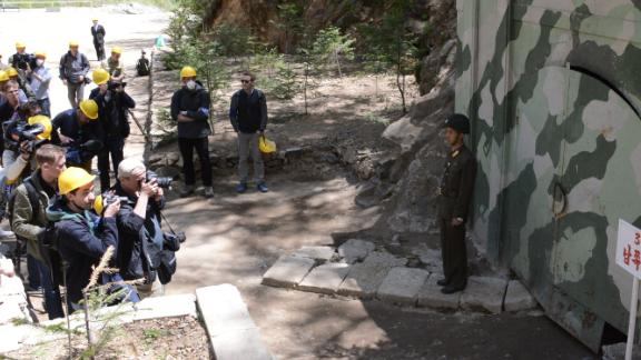 Journalists take photographs at the entrance to tunnel 3.