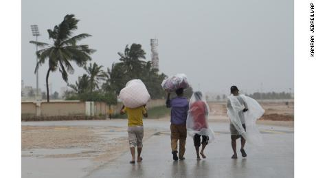 Workers walk to their camp under the rain in Salalah, Oman, on Friday.