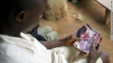 Etienne Ouamouno holds a picture of wife Sia Dembadouno and their son, Emile, in front of their family home in the village of Meliandou, Guinea.
