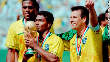 Brazilian forward Romario kisses the FIFA World Cup trophy, flanked by Ronaldao (L) and captain Dunga, after Brazil defeated Italy 3-2 in the shoot-out session (0-0 after extra time) at the end of the World Cup final, 17 July 1994 at the Rose Bowl in Pasadena. Italian Roberto Baggio missed his penalty kick to give Brazil its fourth World Cup title after 1958, 1962 and 1970.    AFP PHOTO/DANIEL GARCIA (Photo by DANIEL GARCIA / AFP)        (Photo credit should read DANIEL GARCIA/AFP/Getty Images)