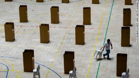 A worker carries chairs at a polling station in Cali, Colombia, on May 25, 2018. - Colombia will hold the first round of the presidential election next May 27. (Photo by Luis ROBAYO / AFP)        (Photo credit should read LUIS ROBAYO/AFP/Getty Images)