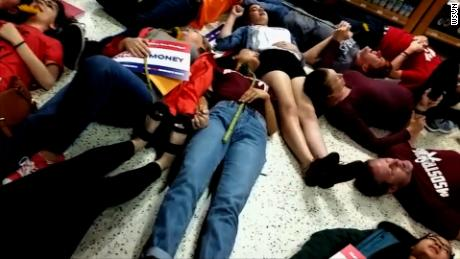 "NS Slug: FL: PUBLIX DIE-IN HELD AGAINST CANDIDATE ADAM PUTNAM  Synopsis: Footage of several Marjory Stoneman Douglas students participating in a protest at a Coral Springs, FL Publix  Video Shows: - Footage of several Marjory Stoneman Douglas students participating in a protest at a Coral Springs, FL Publix by drawing chalk outlines in the parking lot and lied down for exactly 12 minutes in the store. - MSD student David Hogg called for a boycott of Publix due to them donating to gubernatorial candidate Adam Putnam, who has an ""A"" rating from the NRA.   Keywords: FLORIDA PUBLIX PROTEST NRA GUN SUPPORT"
