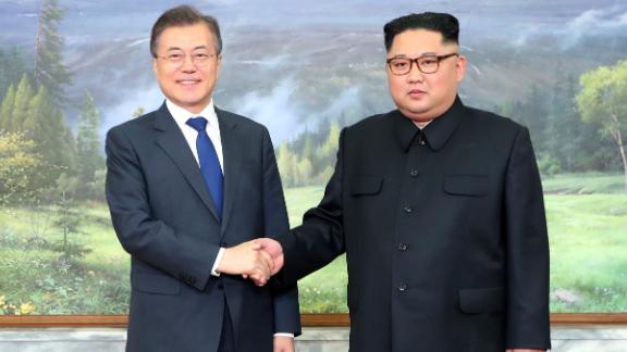 The North and South Korean leaders greet each other before Saturday's meeting.