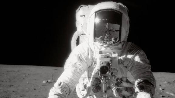 Bean pauses near a tool carrier during the Apollo 12 spacewalk on the moon's surface.