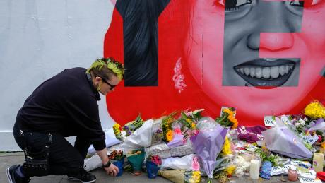 A woman leaves flowers at the Savita Halappanavar mural in Dublin on Saturday.