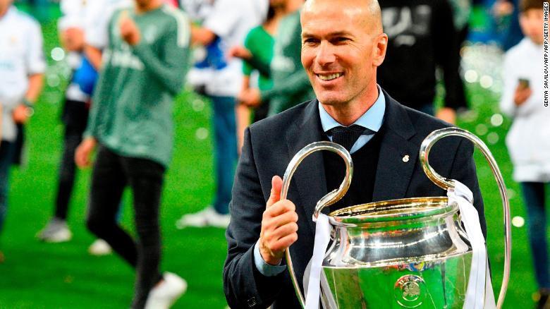 Real Madrid's French coach Zinedine Zidane poses with the trophy after winning  the UEFA Champions League final  against Liverpool.