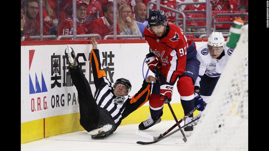 A linesman is upended as Evgeny Kuznetsov (92) of the Washington Capitals and Ondrej Palat (18) of the Tampa Bay Lightning vie for possession in game six of the Eastern Conference Finals during the 2018 NHL Stanley Cup Playoffs in Washington, DC, on Monday, May 21.
