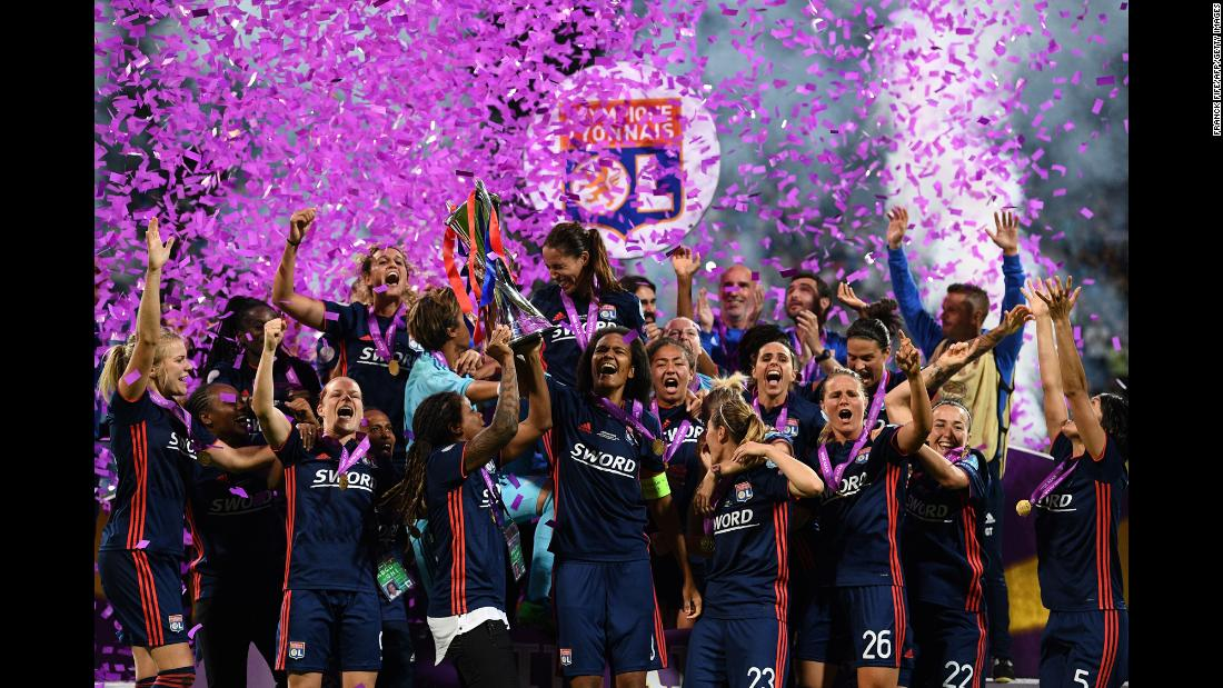 Olympique Lyonnais' French defender Wendie Renard, center, holds the trophy as she and teammates celebrate victory in the UEFA Women's Champions League final football match against Vfl Wolfsburg in Kiev, Ukraine, on Thursday, May 24. Olympique Lyonnais won 4-1, their third trophy in a row.