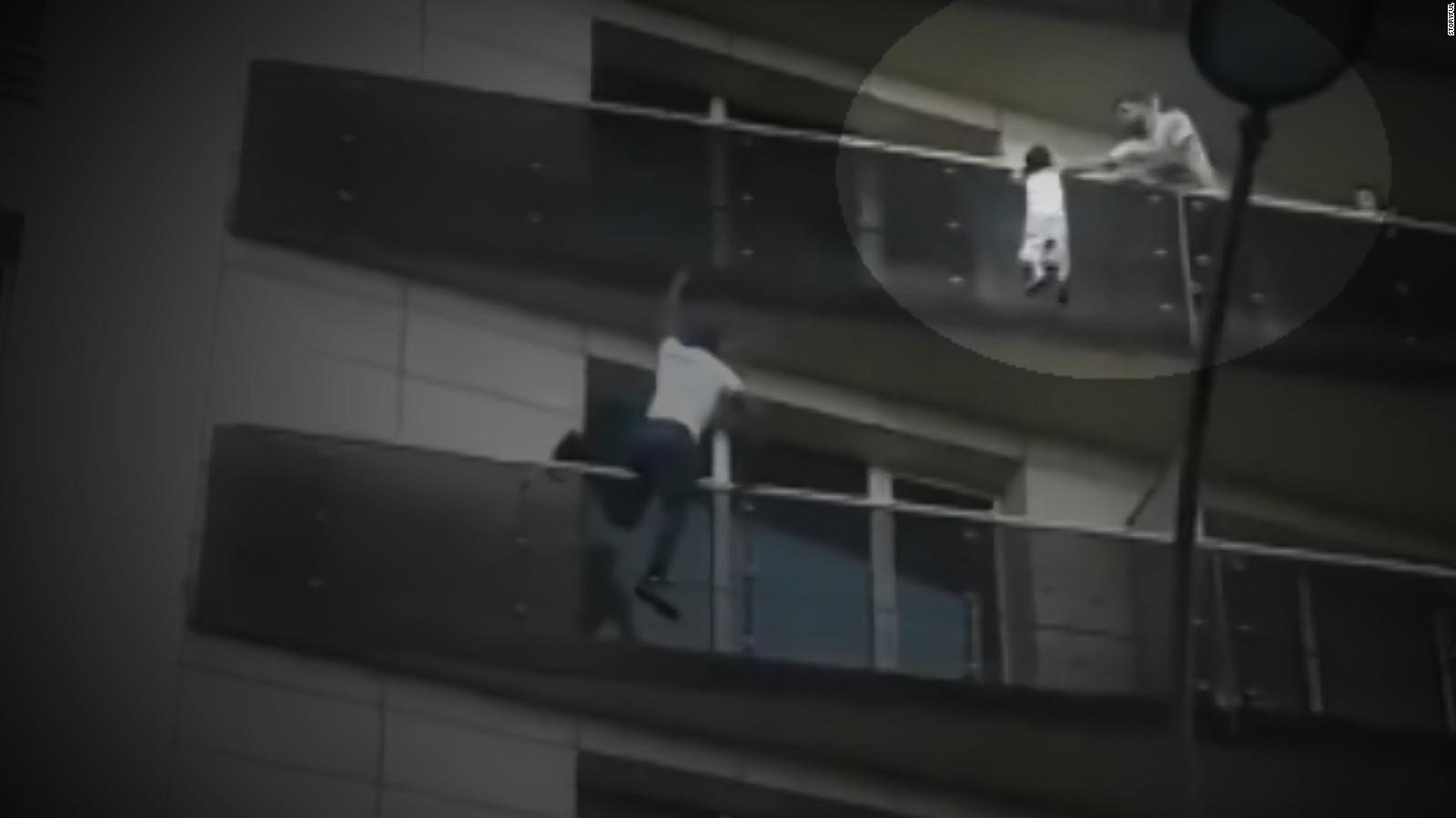 Man scales building to save dangling child - CNN Video