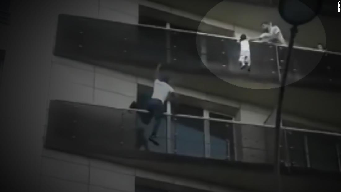 Moment man climbs building to save child