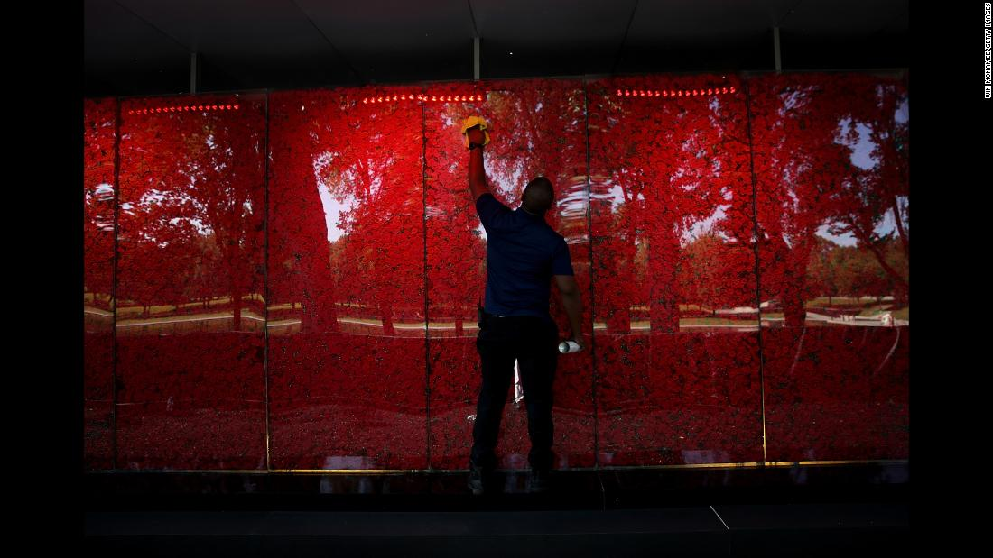 "Romel Martin cleans glass panels while assisting with the installation of a temporary pop-up ""Poppy Memorial"" on the National Mall near the Lincoln Memorial in advance of Memorial Day May 25, 2018 in Washington, DC. (Win McNamee/Getty Images)"