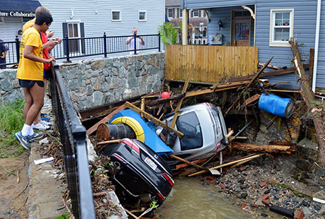 Residents gather by a bridge to look at cars left crumpled in one of the tributaries of the Patapsco River that burst its banks as it channeled through Ellicott City.