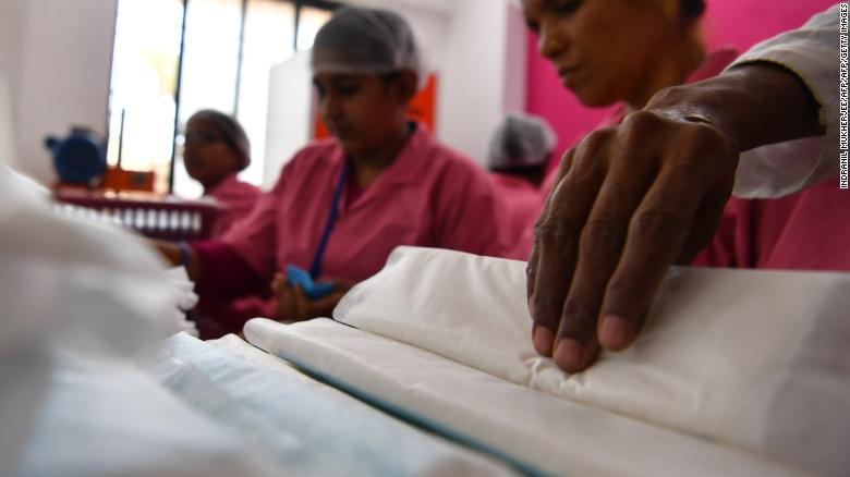 Women working at the Myna Mahila Foundation preparing sanitary pads.