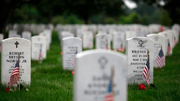 Headstones are adorned with flags at Arlington National Cemetery on Memorial Day, May 27, 2018 in Arlington, Virginia. Mourners from throughout the United States travel to Arlington to visit their loved ones on Memorial Day.