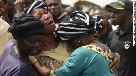 A woman cries as she consoles a widow during a funeral service for people killed in clashes between cattle herders and farmers on January 11, 2018 in Nigeria's Benue state.