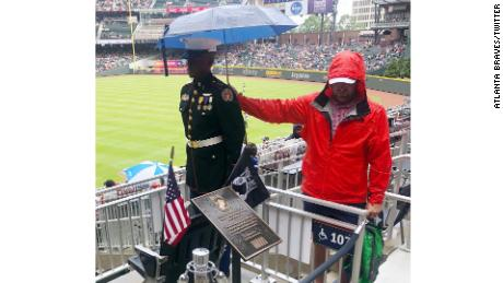 A  fan shields a JROTC member from the rain at the Atlanta Braves game on Monday.