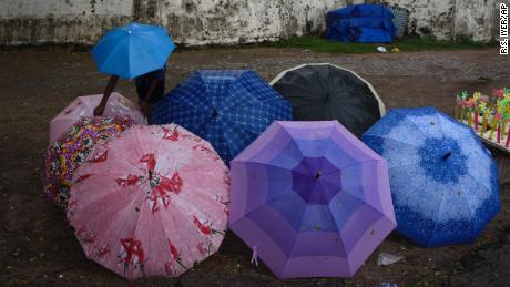 A boy displays umbrellas for sale in Kerala in Southern India, where the annual monsoon has arrived. While the monsoon hasn't yet made it to the northern part of the country, thunderstorms and lightning strikes there have killed 48 people in the past two days.