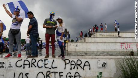 "Anti-government demonstrators standing above a graffiti reading ""Jail for the Ortegas"" hold a protest demanding Nicaraguan President Daniel Ortega and his wife, Vice President Rosario Murillo, to stand down, in Managua on May 26, 2018. - Hundreds of protesters dug in around Nicaragua on Saturday, blocking roads as at least eight more people were killed in a 24-hour period. Unrest has resumed since week-long church-mediated talks between the government and opposition to quell a month of violence broke down late on Wednesday. (Photo by Inti OCON / AFP)        (Photo credit should read INTI OCON/AFP/Getty Images)"