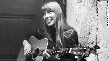 18th September 1968: Canadian folk singer and songwriter Joni Mitchell, strumming her guitar outside The Revolution club in London. (Photo by Central Press/Getty Images)