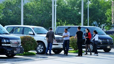 This photo taken on May 23, 2018 shows people looking at imported cars at Qingdao International Auto Mall in Qingdao in China's eastern Shandong province. - China announced on May 22 that it would cut tariffs on auto imports from July 1, the latest sign of a thaw in trade frictions with the United States. (Photo by - / AFP) / China OUT        (Photo credit should read -/AFP/Getty Images)