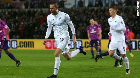 Swansea City's Icelandic midfielder Gylfi Sigurdsson celebrates after scoring the opening goal from the penalty spot during the English Premier League football match between Swansea City and Sunderland at The Liberty Stadium in Swansea, south Wales on December 10, 2016. / AFP / Geoff CADDICK / RESTRICTED TO EDITORIAL USE. No use with unauthorized audio, video, data, fixture lists, club/league logos or 'live' services. Online in-match use limited to 75 images, no video emulation. No use in betting, games or single club/league/player publications.  /         (Photo credit should read GEOFF CADDICK/AFP/Getty Images)