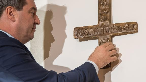 Markus Soder, Bavarian state premier, hangs a cross in the entrance area of the Bavarian State Chancellery in April.
