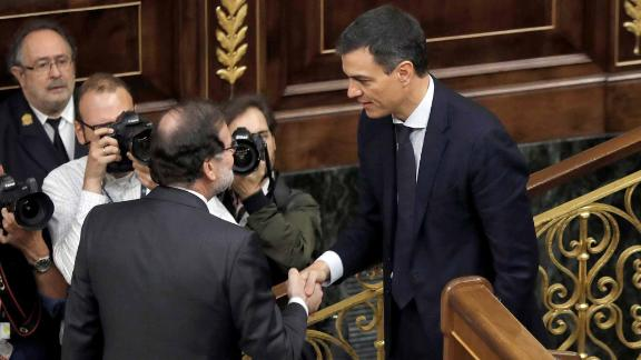 Outgoing Prime Minister Mariano Rajoy, left, shakes hands with Spain
