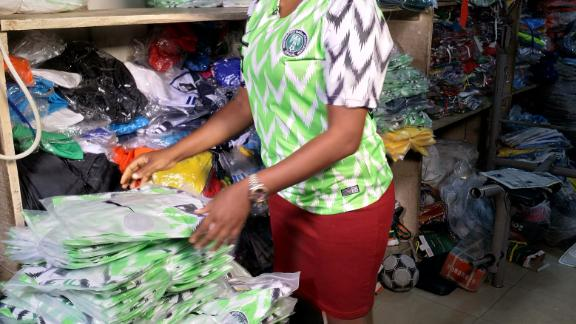 A counterfeit kit seller sorts her wares in her shop in Lagos on May 31 2018 ahead of the official release of the Nigeria World Cup kit.
