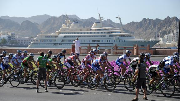 Cyclists ride past the Sultan of Oman