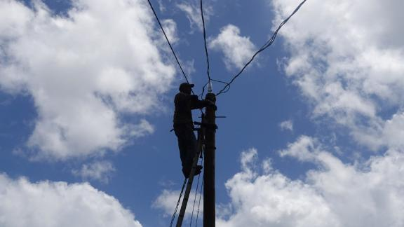 Charley Reyes works to restore power in the Paso Palmas community of Utuado.