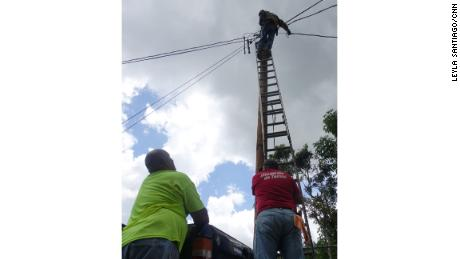Neighbors from Paso Palmas community use old power lines found on the side of the road and splice them together to run new lines of power.