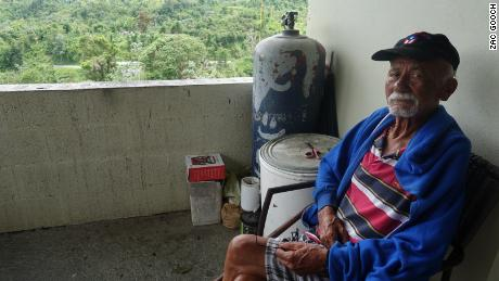 Miguel Angel Vera Gonzalez spends much of his day sitting outside his front door and enjoying the views. His Utuado home still doesn't have power