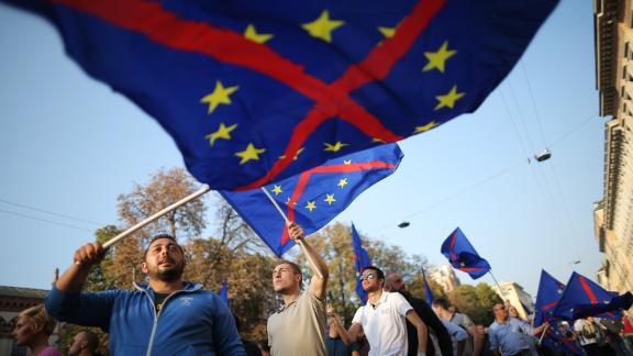 Supporters of the federalist and regionalist Italian political party, Lega Nord, and far-right activists wave a flag of the European Union with a red cross during a demonstration against immigration on October 18, 2014 in Milan.  AFP PHOTO / MARCO BERTORELLO        (Photo credit should read MARCO BERTORELLO/AFP/Getty Images)