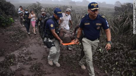 Police officers carry a wounded man after the eruption of the Fuego Volcano, in El Rodeo village.