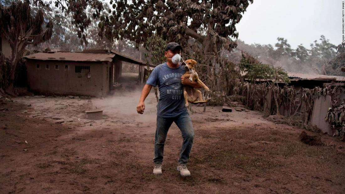 A man carries his dog in San Miguel Los Lotes.