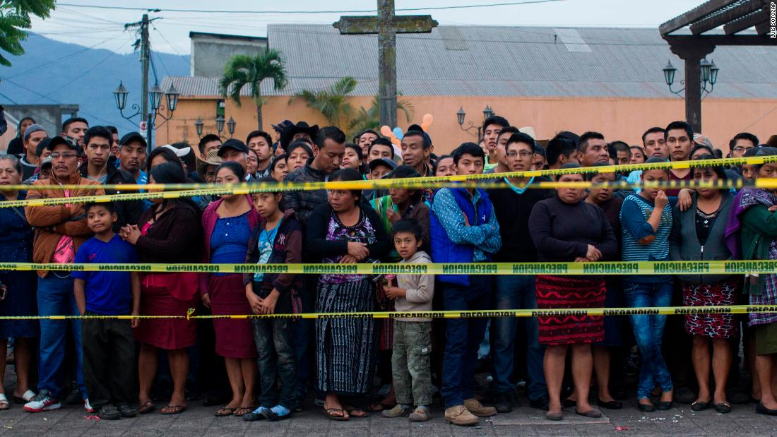 Neighbors stand outside a temporary morgue in Alotenango.