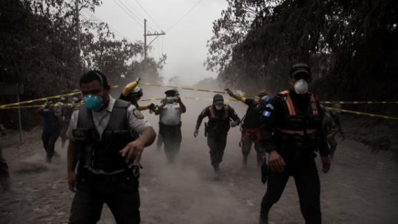 Police officers help people evacuate El Porvenir on June 3.