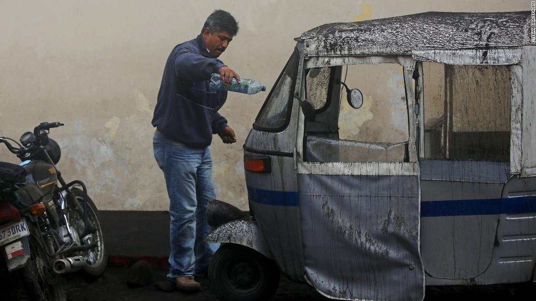 A man cleans his motorcycle taxi, which was covered in ash in Antigua.