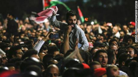 Jordanian protesters shout slogans and raise a national flag during a demonstration outside the Prime Minister's office in the capital Amman late on Friday.
