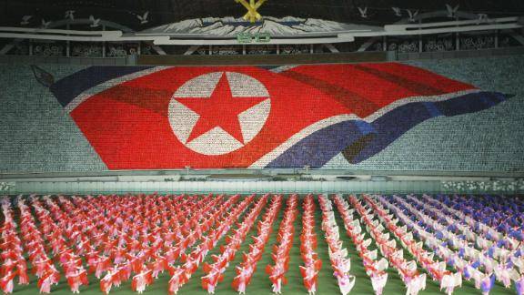 PYONGYANG, NORTH KOREA - OCTOBER 6: North Koreans perform showing North Korean national flag during the Arirang festival which is a part of commemorations marking the 60th anniversary of the Workers