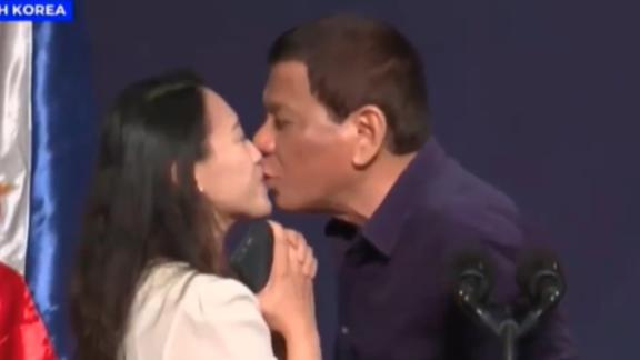 Philippines President Rodrigo Duterte kissing a Filipino woman on stage during a visit to South Korea in 2018.
