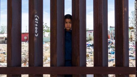 A young boy peers from the Mexican side of the US-Mexico border fence in Anapra, Texas.